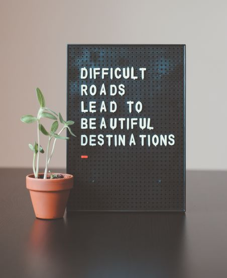 Image of desk decoration with text saying difficult roads lead to beautiful destinations.